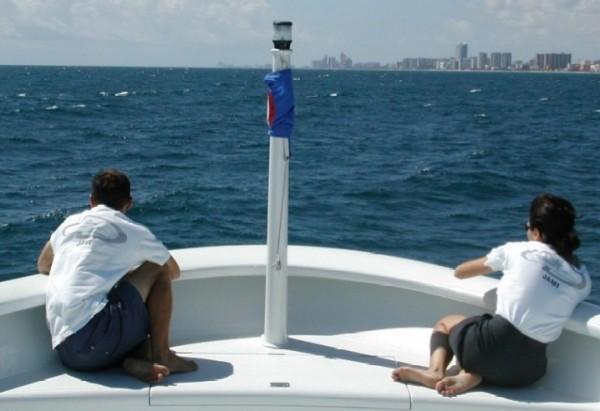 Megayacht crew taking a break on the bow as they sail around Miami.