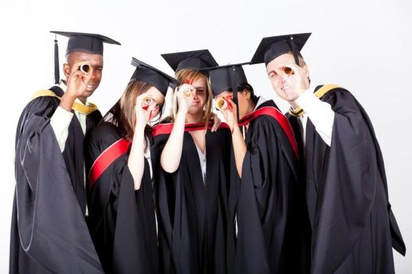 group of graduates looking through their diploma