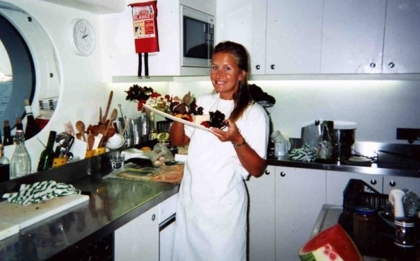 A yacht Stewardess assists the chef in the Galley