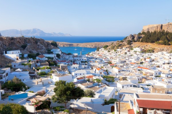 Lindos, Greece. White houses of the village of Lindos, a fortress on the hill and the beautiful bay.